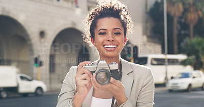 Buy stock photo Cropped shot of an attractive young woman standing alone in the city and using her camera to take pictures