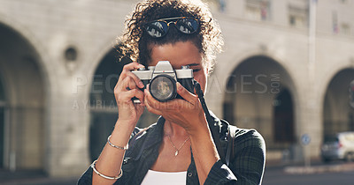 Buy stock photo Cropped shot of an attractive young woman standing alone in the city and taking a picture with her camera