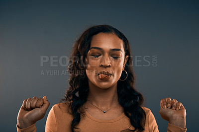 Buy stock photo Studio shot of an attractive young woman sticking her tongue out with her eyes closed while standing against a grey background