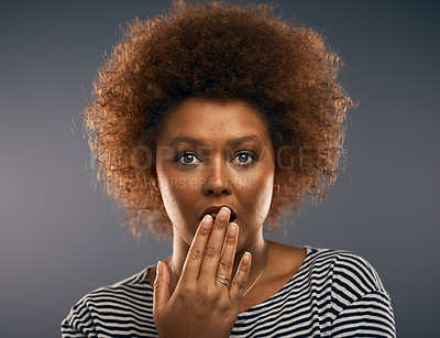 Buy stock photo Studio portrait of an attractive young woman looking shocked while standing against a grey background
