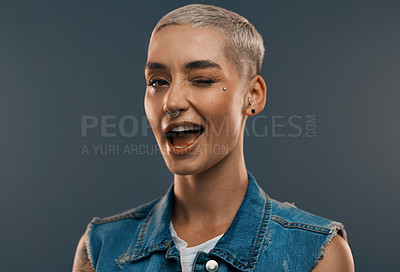 Buy stock photo Studio portrait of an attractive young woman winking while standing against a grey background