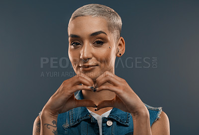 Buy stock photo Studio portrait of an attractive young woman making a heart shape with her hands while standing against a grey background