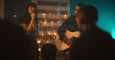 Buy stock photo Shot of a young man and woman performing on stage in a club