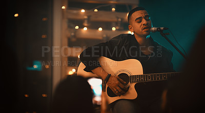 Buy stock photo Shot of a young man singing and playing the guitar on stage