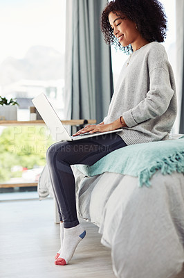 Buy stock photo Cropped shot of an attractive young woman sitting on her bed and using her laptop at home