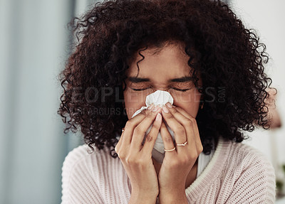 Buy stock photo Cropped shot of an attractive young woman sitting on her bed and suffering from a cold at home