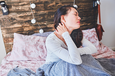 Buy stock photo Shot of a young woman sitting in bed and suffering from neck ache at home