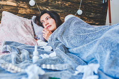 Buy stock photo Shot of a young woman sick in bed at home