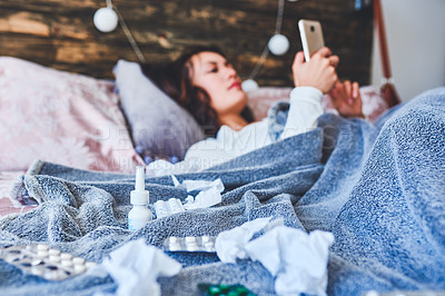 Buy stock photo Shot of a young woman using a smartphone while sick in bed at home