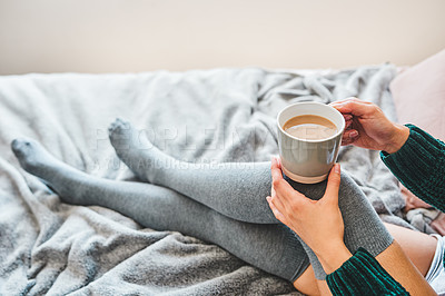 Buy stock photo Cropped shot of an unrecognizable woman having coffee while sitting on her bed