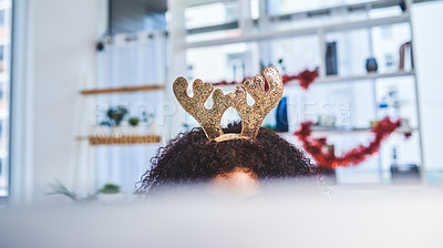 Buy stock photo Cropped shot of an unrecognizable businesswoman sitting alone in her office and using her computer while wearing christmas headgear