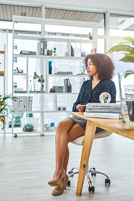 Buy stock photo Full length shot of an attractive young businesswoman sitting alone in her office and looking contemplative while holding a tablet