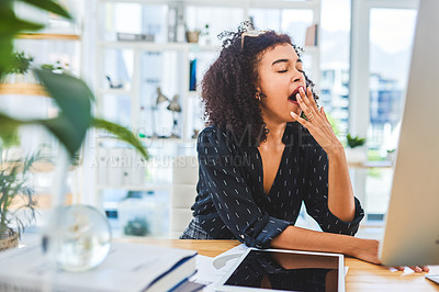 Buy stock photo Cropped shot of an attractive young businesswoman sitting alone in her office and yawning while feeling sleepy
