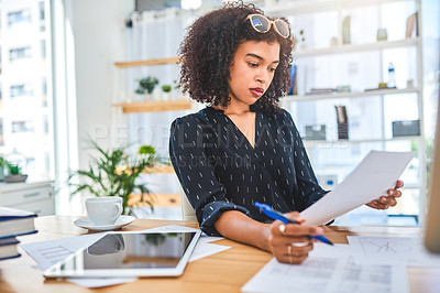Buy stock photo Cropped shot of an attractive young businesswoman sitting alone in the office and going through paperwork