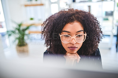 Buy stock photo Cropped shot of an attractive young businesswoman sitting alone in her office with her hand on her chin