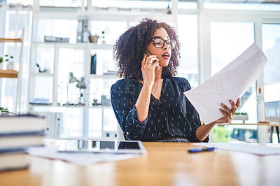 Buy stock photo Cropped shot of an attractive young businesswoman sitting alone in the office and going through paperwork while using her cellphone
