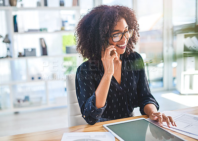 Buy stock photo Cropped shot of an attractive young businesswoman sitting alone in the office and talking on her cellphone