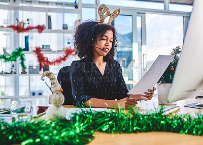 Buy stock photo Cropped shot of an attractive young customer service agent sitting in the office and reading paperwork while wearing christmas decorations
