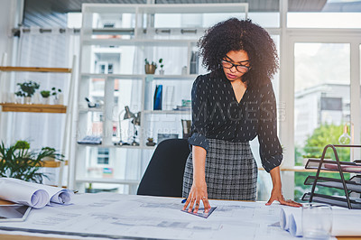 Buy stock photo Shot of a young businesswoman working with blueprints in an office