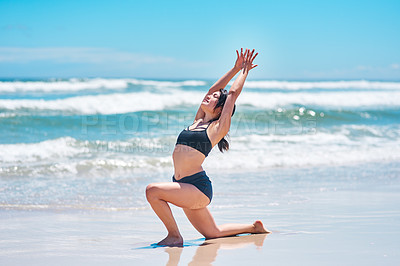 Buy stock photo Shot of a young woman practising yoga at the beach