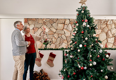 Buy stock photo Cropped shot of a cheerful mature couple looking at a fully decorated Christmas tree inside at home during the day