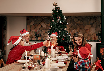 Buy stock photo Cropped shot of a cheerful family having a celebratory toast while having dinner during Christmas eve at home