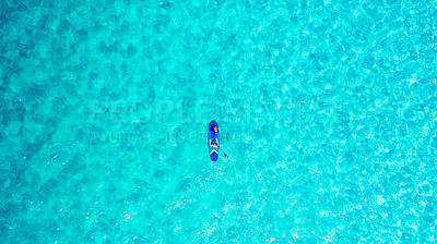 Buy stock photo High angle shot of a man paddle boarding across the sea