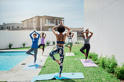 Buy stock photo Shot of a group of young women doing yoga together in a garden