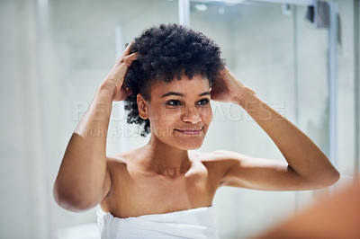 Buy stock photo Cropped shot of a confident young woman standing in front of a mirror while touching her hair inside of a bathroom during the morning hours