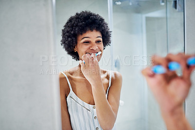 Buy stock photo Cropped shot of a cheerful young woman looking into a mirror while brushing her teeth inside of a bathroom