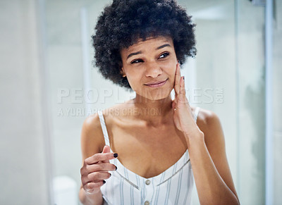 Buy stock photo Cropped shot of a confident young woman standing in front of a mirror while touching her face inside of a bathroom during the morning hours