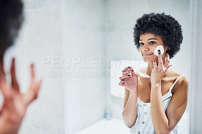 Buy stock photo Cropped shot of a cheerful young woman applying a toner on her face with a cotton pad while looking into a mirror inside of a bathroom