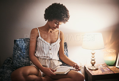 Buy stock photo Cropped shot of an attractive young woman sitting alone on her bed at home and reading her bible at night