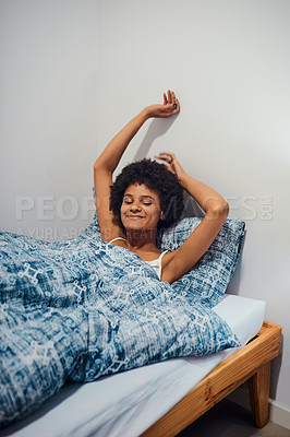 Buy stock photo Cropped shot of an attractive young woman lying in her bed alone at home and stretching while waking up