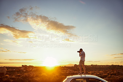 Buy stock photo Shot of a young man taking photos while standing on top of a car in a rural landscape