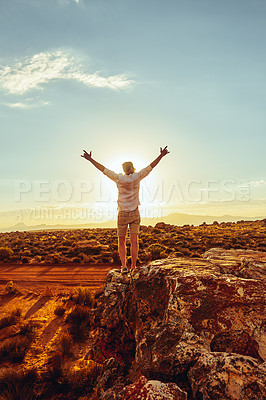 Buy stock photo Rearview shot of a young man standing with his arms outstretched in a rural landscape