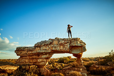 Buy stock photo Shot of a young woman standing on a cliff in a rural landscape