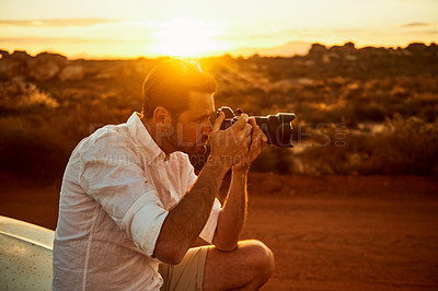 Buy stock photo Shot of a young man taking photos in a rural landscape