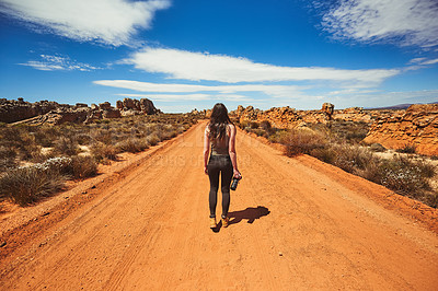 Buy stock photo Rearview shot of a young woman holding a camera while standing on a dirt road in a rural landscape