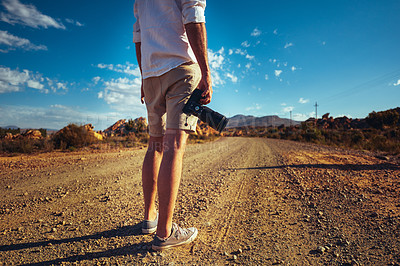 Buy stock photo Rearview shot of a young man holding a camera while standing on a dirt road in a rural landscape