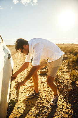 Buy stock photo Shot of a young man inspecting a flat tyre on his car in a rural area