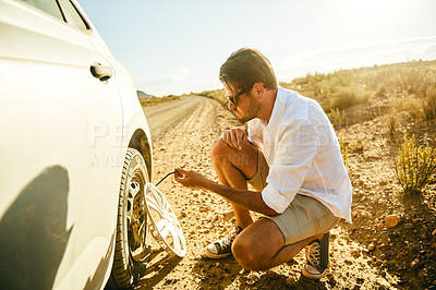 Buy stock photo Shot of a young man pulling a nail out from a flat tyre on his car in a rural area