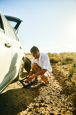 Buy stock photo Shot of a young man changing a flat tyre on his car in a rural area