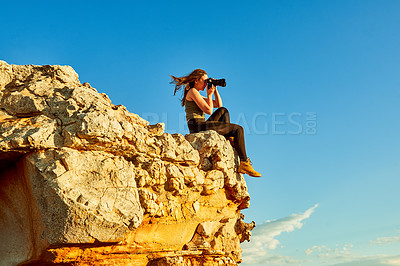 Buy stock photo Shot of a young woman taking photos while sitting on a cliff in a rural landscape