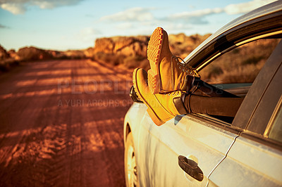 Buy stock photo Shot of an unrecognisable woman's legs hanging out a car window during a road trip in a rural landscape