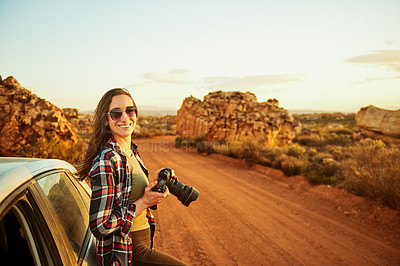 Buy stock photo Portrait of a young woman taking photos while on a road trip in a rural landscape