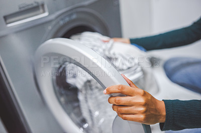 Buy stock photo Closeup shot of an unrecognisable woman using a washing machine to do laundry at home