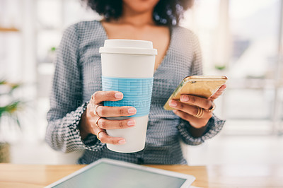Buy stock photo Cropped shot of a young businesswoman drinking coffee while using her cellphone at the office