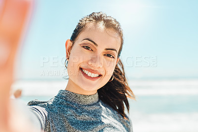 Buy stock photo Shot of a fit young woman taking a selfie during a workout at the beach