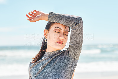 Buy stock photo Shot of a fit young woman taking a break during a workout at the beach
